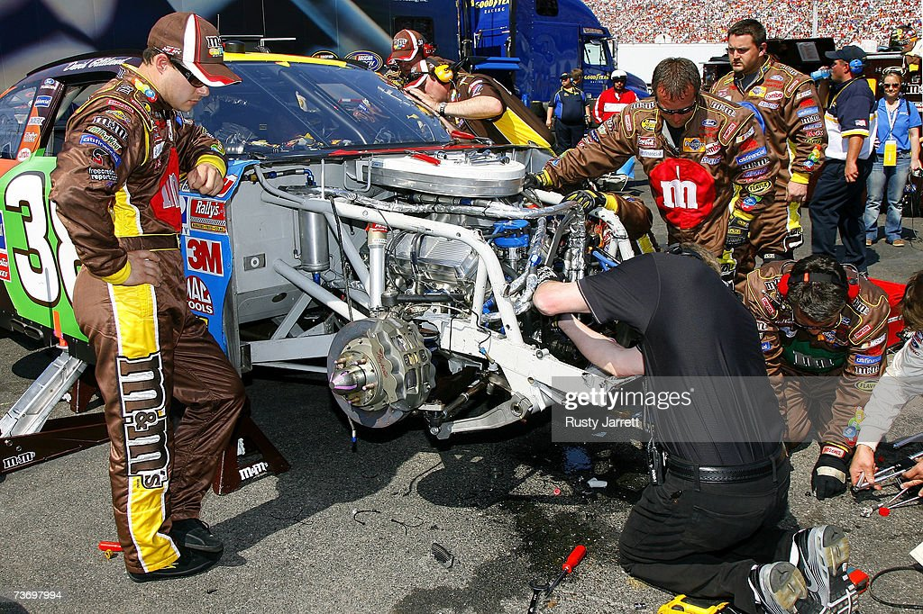 The damaged car of David Gilliland driver of the MM's Ford is worked on behind the wall after crashing during the NASCAR Nextel Cup Series Food City...