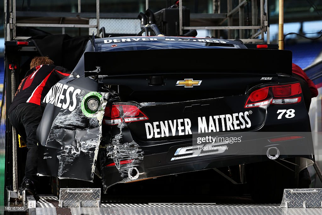 The damaged Kurt Busch, driver of the #78 Furniture Row / Denver Mattress Chevrolet, is loaded onto the hauler after an on track incident during practice for the NASCAR Sprint Cup Series 13th Annual Hollywood Casino 400 at Kansas Speedway on October 5, 2013 in Kansas City, Kansas.