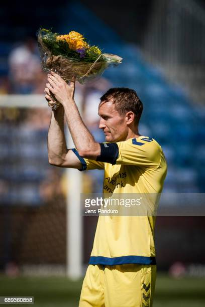 Thomas Kahlenberg of Brondby IF is presented with flowers by Troels Bech from Brondby BRONDBY DENMARK MAY 28 the Danish Alka Superliga match between...