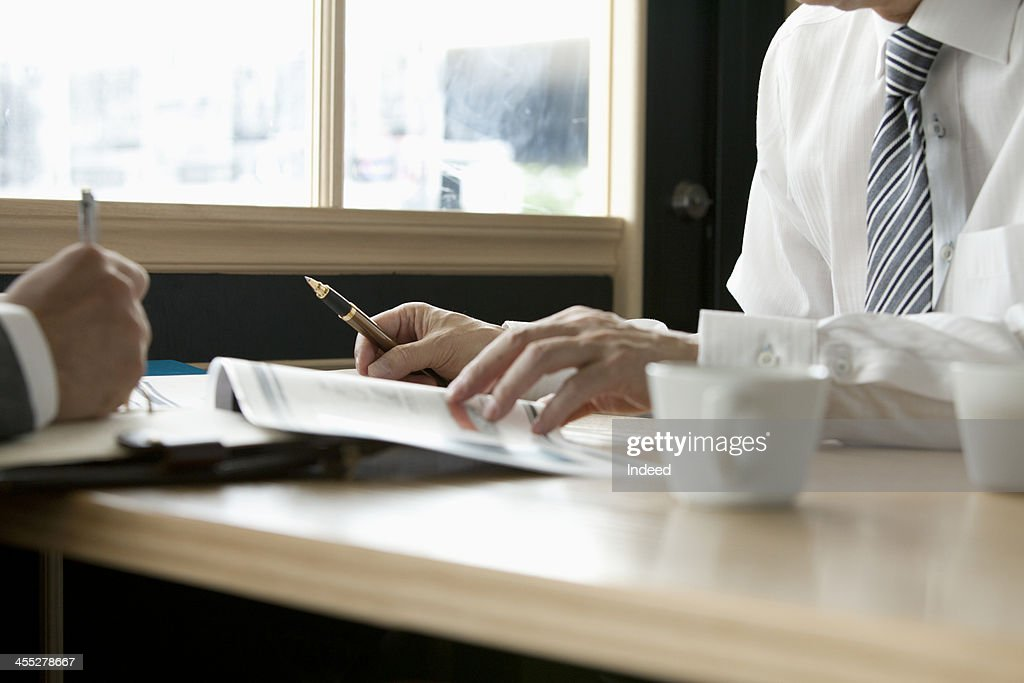 BUSINESS SCENE The data and the hand on a table : Stock Photo