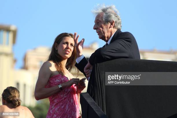 The daughter of Caroline Princess of Hanover Hereditary Princess of Monaco Charlotte Casiraghi speaks with French actor Jean Rochefort during the...