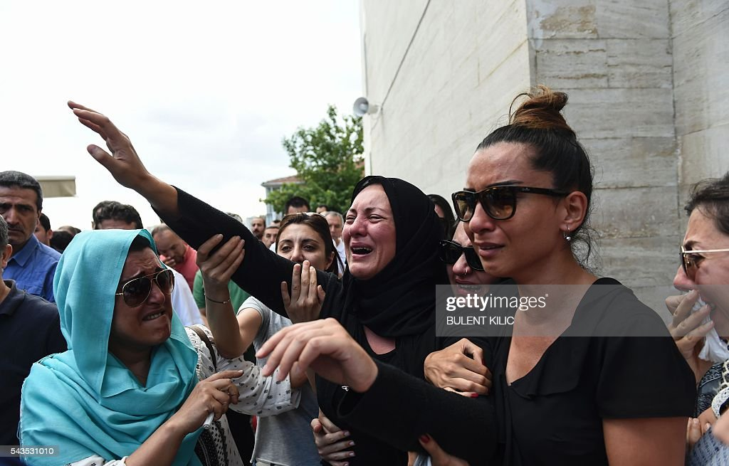The daughter of Siddik Turgan, who was killed in the June 28, 2016 airport attack, reacts as her father's coffin is carried nearby during his funeral ceremony on June 29, 2016 in Istanbul, a day after a suicide bombing and gun attack targeted Istanbul's airport, killing at least 41 people. Turkey declared on June 29, 2016 a day of national mourning over a deadly attack at Istanbul's international airport blamed by the government on Islamic State jihadists. / AFP / BULENT