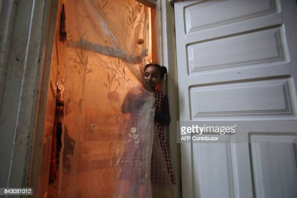 The daughter of Zahraa Abdi who fled her native Somalia in 2012 with her three children stands behind a curtain inside a shared apartment in the...