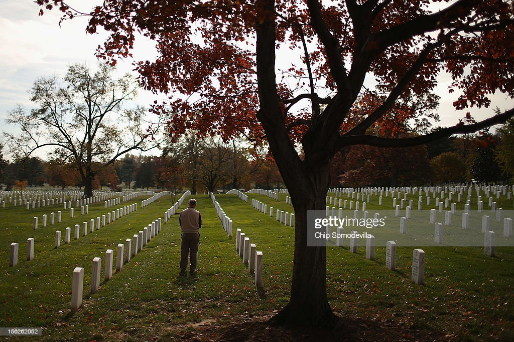 The day after Veterans Day, a man pauses between rows of headstones at Arlington National Cemetery November 12, 2012 in Arlington, Virginia. The federal government observed Veterans Day by giving employees Monday off from work.