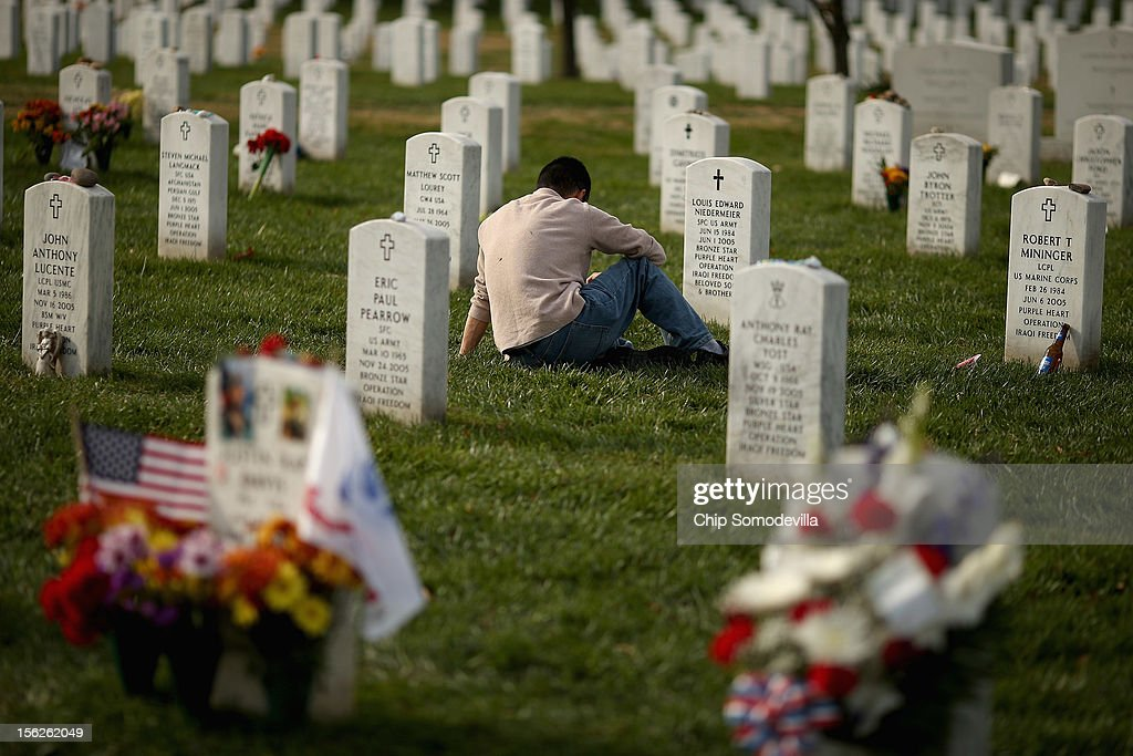 The day after Veterans Day, a man pauses between rows of headstones in Section 60, where most casualties of the wars in Afghanistan and Iraq are buried at Arlington National Cemetery, November 12, 2012 in Arlington, Virginia. The federal government observed Veterans Day by giving employees Monday off from work.