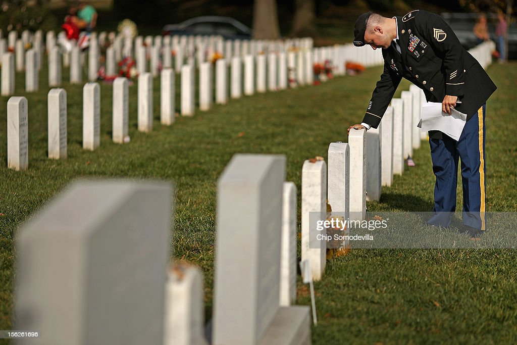 The day after Veterans Day, U.S. Army Staff Sgt. Luke Parrott touches the headstone of a fellow soldier and friend in Section 60 at Arlington National Cemetery November 12, 2012 in Arlington, Virginia. A veteran of the wars in Afghanistan and Iraq, Parrott was injured in an IED blast in Baghdad in 2005. Parrott spent time sitting and talking to the graves of the soldiers he knew. 'It's as close as we can get to talking anymore,' he said.