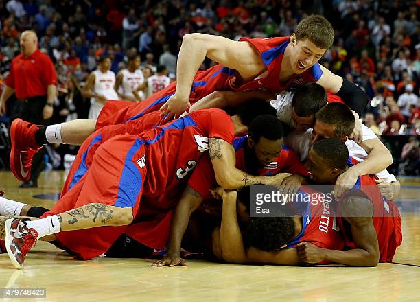 The Dayton Flyers celebrate after defeating the Ohio State Buckeyes 6059 in the second round of the 2014 NCAA Men's Basketball Tournament at the...