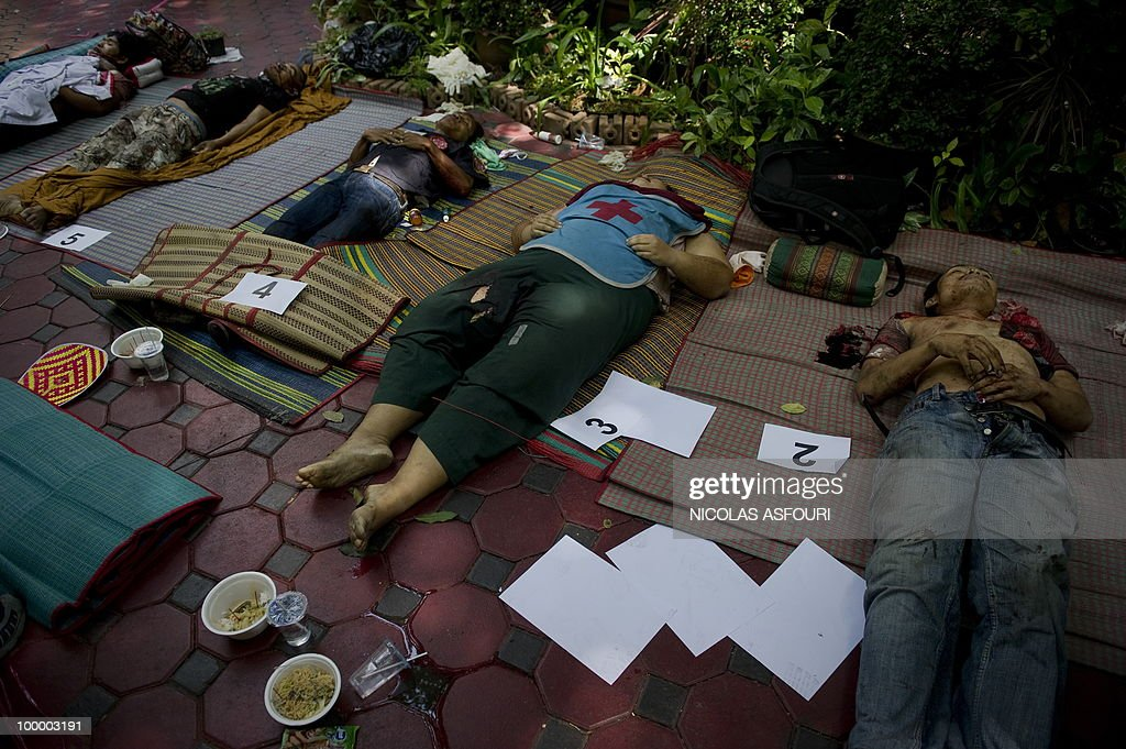 The dead bodies of anti-government protesters killed in a gunbattle the day before lie on mats at a temple which had been turned into a shelter within an anti-government protest site in downtown Bangkok on May 20, 2010. Gunshots rang out near a Buddhist temple in the heart of an anti-government protest zone in Bangkok, and soldiers were advancing on foot along an elevated train track, an AFP photographer saw. Thai security forces stormed the 'Red Shirts' protest camp on May 19 in a bloody assault that forced the surrender of the movement's leaders who asked their supporters to disperse. AFP PHOTO/ Nicolas ASFOURI