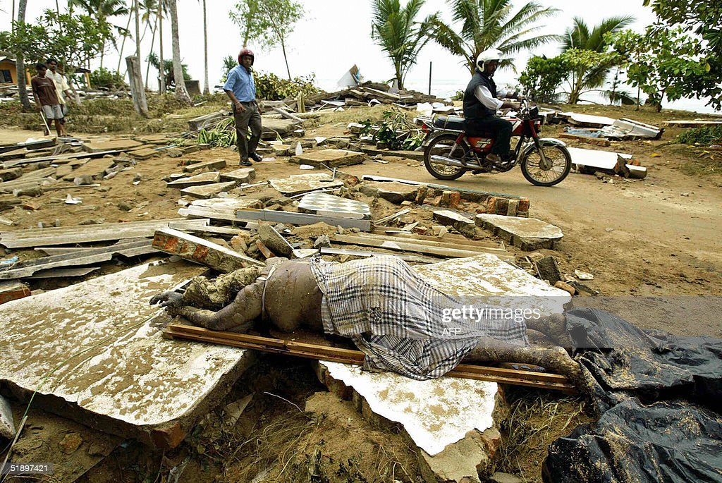 The dead body of a Sri Lankan resident lies amid rubble of destroyed houses in the southern coastal town of Matara 28 December 2004 after the region...