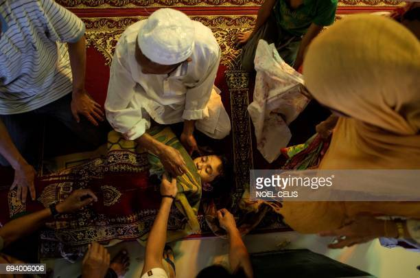 TOPSHOT The dead body of Abdillah Masid is surrounded by his family inside Camp Ranao Mosque in Barangay Saber in Marawi on the southern Philippine...
