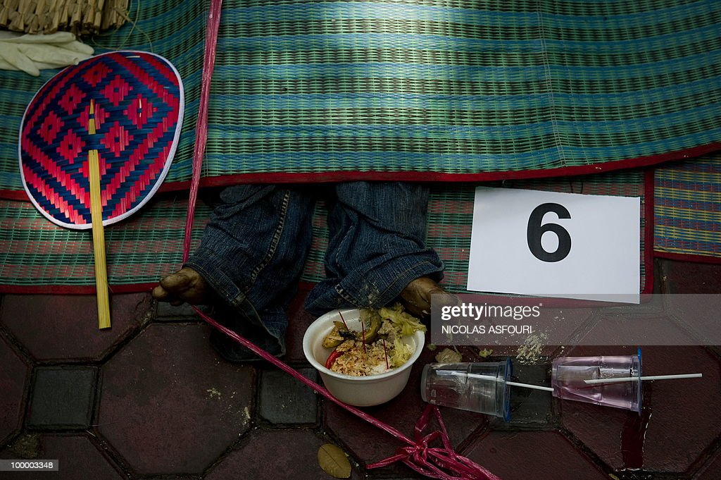 The dead body of an anti-government protester killed in a gunbattle the day before lies on a mat at a temple which had been turned into a shelter within an anti-government protest site in downtown Bangkok on May 20, 2010. Gunshots rang out near a Buddhist temple in the heart of an anti-government protest zone in Bangkok, and soldiers were advancing on foot along an elevated train track, an AFP photographer saw. Thai security forces stormed the 'Red Shirts' protest camp on May 19 in a bloody assault that forced the surrender of the movement's leaders who asked their supporters to disperse. AFP PHOTO/ Nicolas ASFOURI