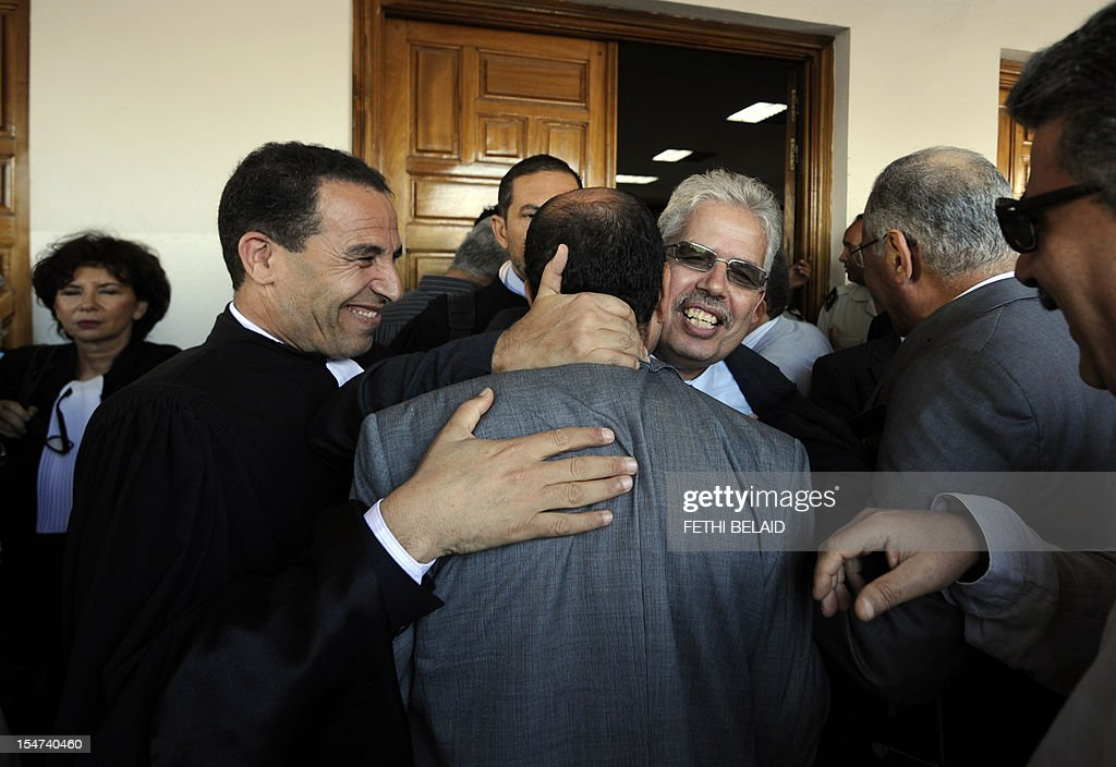 The dean of the faculty of arts, letters and humanities at Manouba University, Kazdaghli Habib (C-background), greets his lawyer and human rights defender Chokri Belaid (C) outside the Manouba court, near Tunis, on October 25, 2012, upon his arrival for the opening of his trial on charges of allegedly slapping a female student wearing a niqab. Kazdaghli said that the student who lodged a complaint against him was expelled from his faculty for six months because she had refused to remove her veil. AFP PHOTO / FETHI BELAID