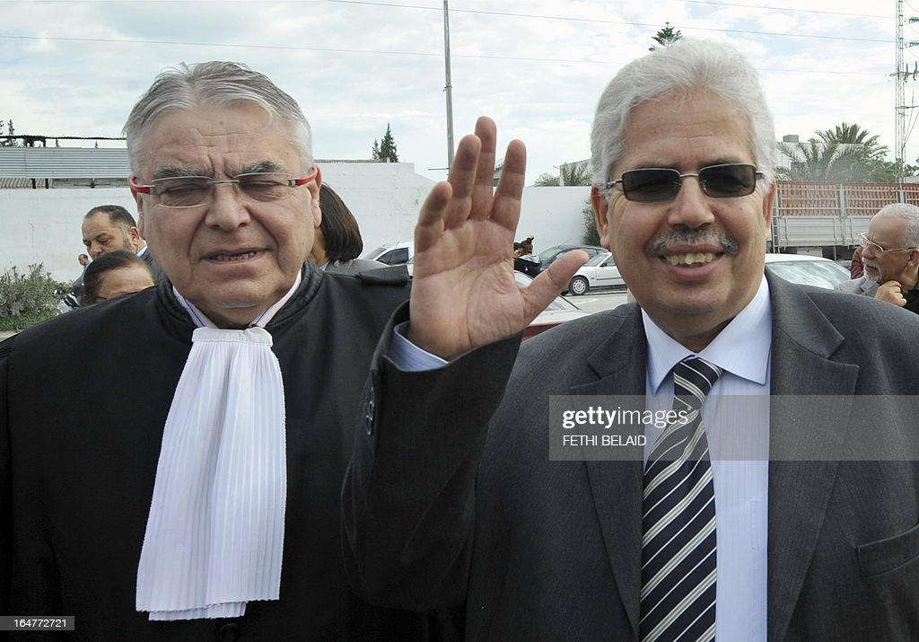 The dean of the faculty of arts, letters and humanities at Manouba University, Habib Kazdaghli (R), accused of slapping a female student wearing an Islamic veil, waves as he arrives at the Manouba court, near Tunis, with his lawyer Laurent Philippe (L) on March 28, 2013. The verdict of Kazdaghli's trial, that has gripped Tunisia for months amid bristling tensions between secularists and hardline Salafists was delayed as hundreds of people protested outside the court. AFP PHOTO / FETHI BELAID