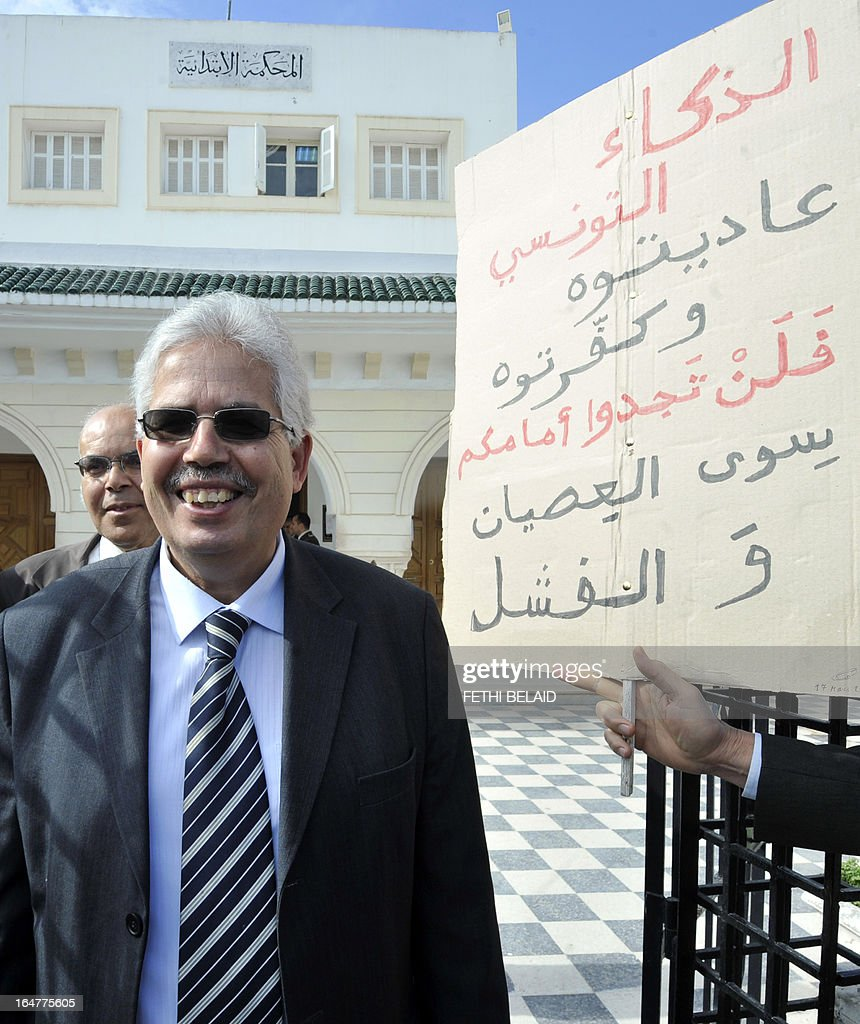 The dean of the faculty of arts, letters and humanities at Manouba University, Habib Kazdaghli, accused of slapping a female student wearing an Islamic veil, leaves the Manouba court near Tunis, on March 28, 2013. The verdict of Kazdaghli's trial, that has gripped Tunisia for months amid bristling tensions between secularists and hardline Salafists, was delayed as hundreds of people protested outside the court. Arabic writing on placard reads 'You have stood against Tunisian intelligence and deemed it blasphemous, you'll find before you only disobedience and failure'.