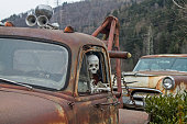 skeleton at the wheel of an old junk cars