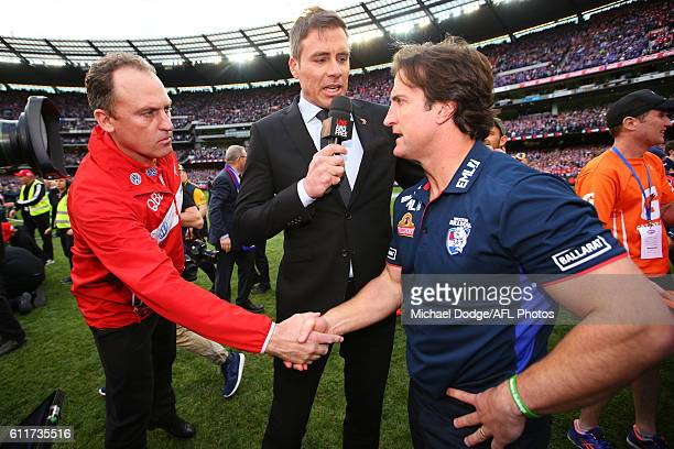 The defeated Swans head coach John Longmire shakes hands with Bulldogs head coach Luke Beveridge during the 2016 AFL Grand Final match between the...