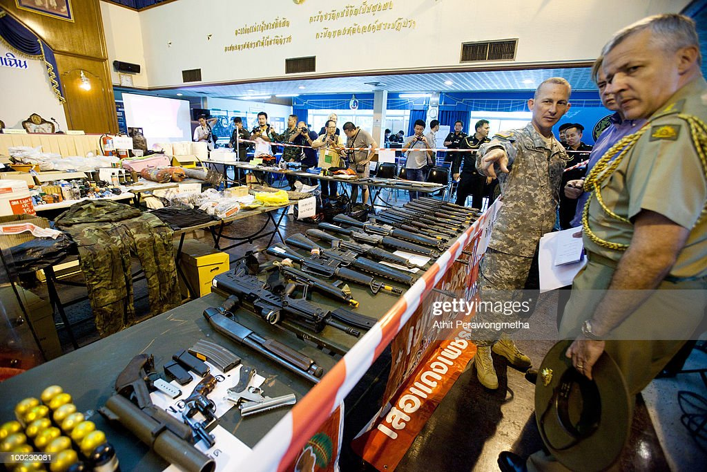 The Defence Attache of Australia, John Blaxland (R) and Defence Attache of USA (2-R) look on weapons seized before a press conference at the 11th Infantry Regiment on May 22, 2010 in Bangkok, Thailand. Thai Prime Minister Abhisit Vejjajiva says order has been restored to the capital Bangkok and throughout the country. A night-time curfew remains in place in Bangkok and 23 provinces accross Thailand in a bid to prevent a resurgence of unrest. At least 44 people have been killed in clashes in which protesters clashed with military forces over a period of six consecutive days, resulting in the end of the blockade and the surrender of Red-shirt leaders.