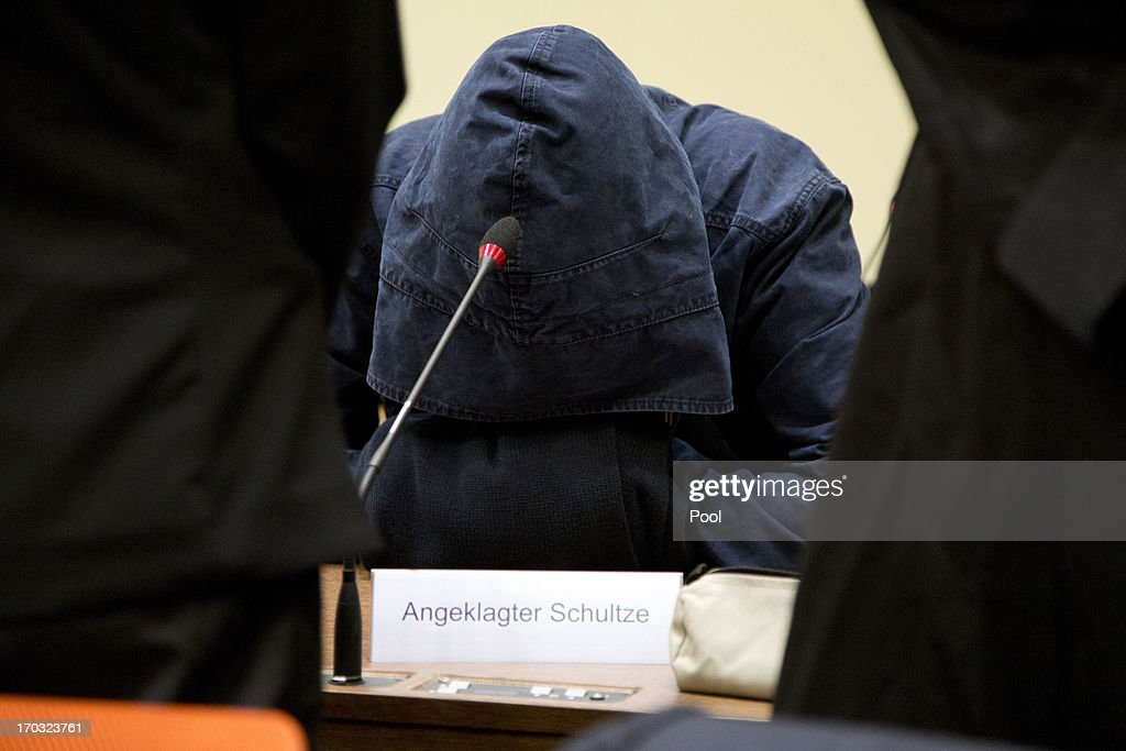 The defendant Carsten S. hides his face under his hood prior to the trial during day eight of the NSU neo-Nazis murder trial at the Oberlandgericht Muenchen court on June 11, 2013 in Munich, Germany. Beate Zschaepe is the main defendant and is on trial for her role in assisting Uwe Boehnhardt and Uwe Mundlos in the murder of nine immigrants and one policewoman across Germany between 2000 and 2007. Together the trio called themselves the NSU, or National Socialist Underground, and were able to operate unbeknownst to police until Mundlos and Boehnhardt were cornered in 2011 after the two robbed a bank. Four other co-defendants, including Ralf Wohlleben, Holder G., Carsten S. and Andre E., are accused of assisting the trio. Carsten S. and Holger G. have declared themselves willing to give limited testimonies, while Zschaepe has thus far remained silent and refuses to answer any questions by the court.