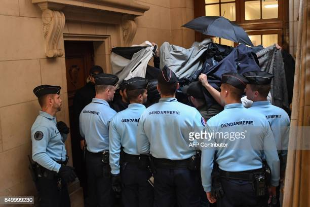 The defendants' friends use blankets and umbrellas to hide them as they arrive as Gendarmes look on on September 20 2017 to the Paris courthouse for...