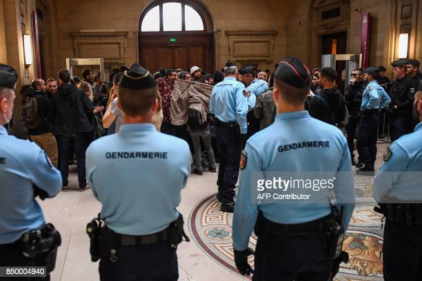 The defendants' friends use blankets to hide them as Gendarmes look on as they arrive on September 20 2017 to the Paris courthouse for the start of...