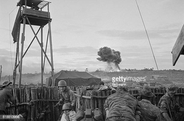 The defenders of besieged Plei Me Special Forces camp watch a bomb burst as American fighter bombers pound a Viet Cong position a short distance away...