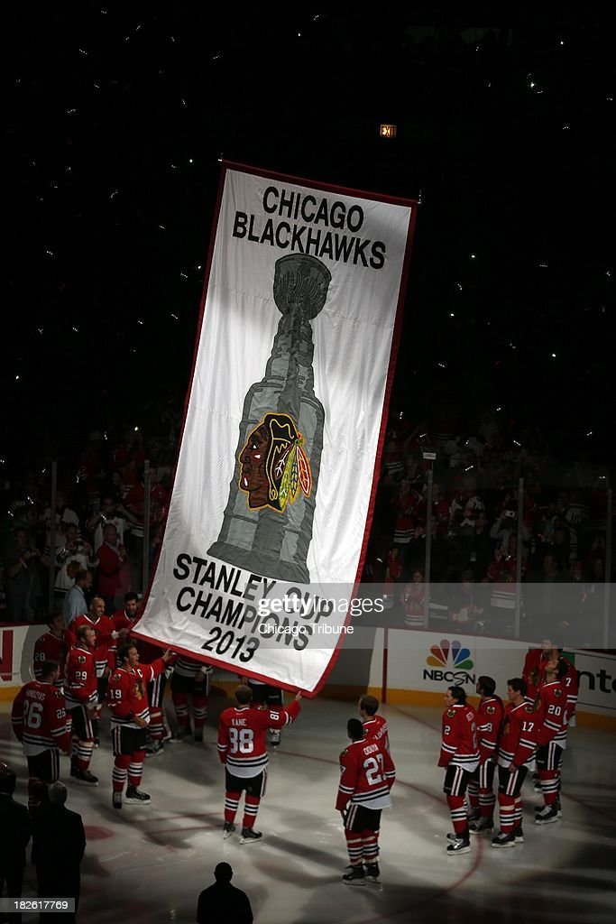 The defending Stanley Cup champion Chicago Blackhawks hoist a banner commemorating their title prior to action against the Washington Capitals at the United Center in Chicago, Illinois, on Tuesday, October 1, 2013.