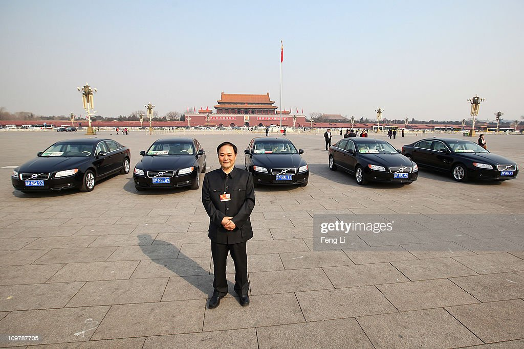 The delegate Li Shufu chairman of China's Geely Holding Group poses for photographs in front of Volvo cars on the Tiananmen Square during the opening...