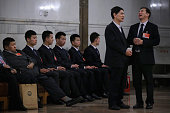 The delegate Mao Xinyu grandson of Chairman Mao Zedong looks on as five soldiers dressed as usher sitting aside before the second plenary session of...