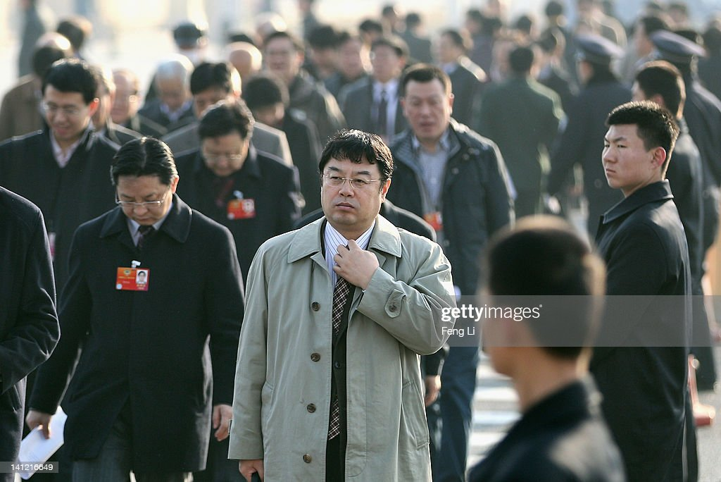 The delegates arrive at the Great Hall of the People as the security guards (Right) stand before the closing ceremony of the Chinese People's Political Consultative Conference (CPPCC) on March 13, 2012 in Beijing, China. Known as 'liang hui,' or 'two organizations', it consists of meetings of China's legislature, the National People's Congress (NPC), and its advisory auxiliary, the Chinese People's Political Consultative Conference (CPPCC).