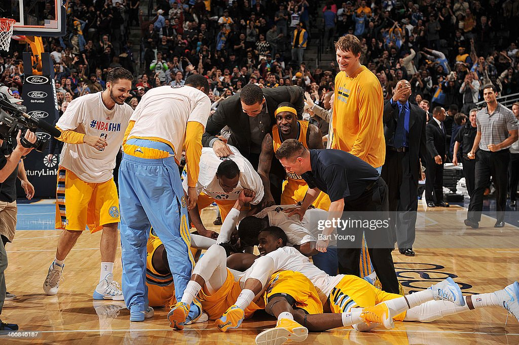 The Denver Nuggets pile on top of <a gi-track='captionPersonalityLinkClicked' href=/galleries/search?phrase=Randy+Foye&family=editorial&specificpeople=240185 ng-click='$event.stopPropagation()'>Randy Foye</a> #4 of the Denver Nuggets after he hits a game winning shot against the Los Angeles Clippers on February 3, 2014 at the Pepsi Center in Denver, Colorado.