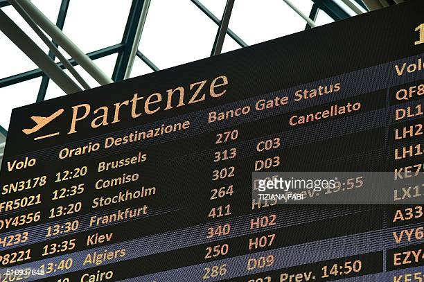 The departure board at Rome's Fiumicino aiport displays the cancellation of flights to Brussels on March 22 in the wake of the series of apparently...