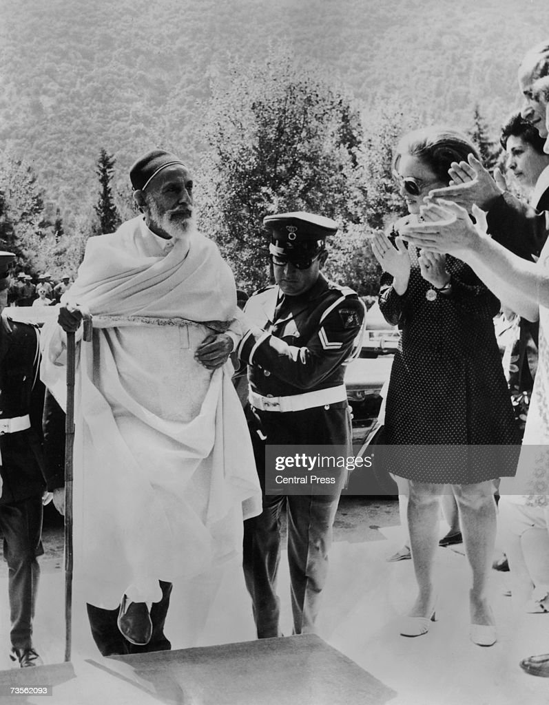 The deposed King Idris I of Libya (1890 - 1983) receives a warm welcome upon his yearly visit to Kamena Vourla in Greece, 6th September 1969. A member of the Greek Tourist Police helps him up the steps.