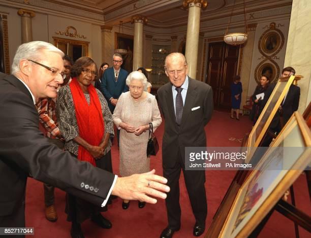The Deputy Australian High Commissioner Andrew Todd shows Queen Elizabeth II and Duke of Edinburgh the work of Albert Namajtira the Aboriginal artist...