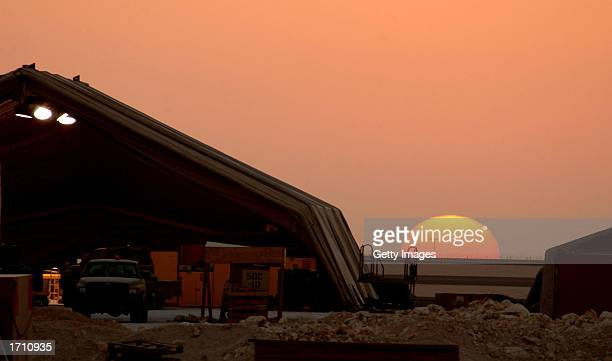 The desert sun sets behind a maintenance hangar at the 379th Air Expeditionary Wing December 30 2002 in Al Udeid Qatar