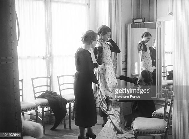 The designer Elsa SCHIAPARELLI fitting a model with a dress in her shop in Paris A worker on her knees checks the measurements