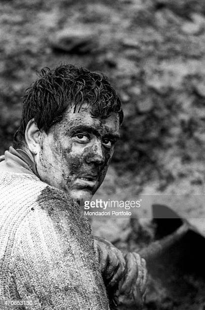 'The despair and confusion in the gaze of a Welsh miner of Aberfan with a face covered in mud after a landslide that destroyed the village on the...