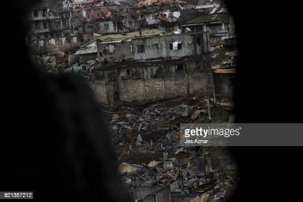The destruction caused by the battle between government troops and militants is seen through a hole on a wall inside a house on July 22 2017 in...