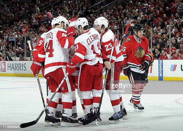 The Detroit Red Wings celebrate after scoring in the second as Fernando Pisani of the Chicago Blackhawks skates away disappointed on April 10 2011 at...