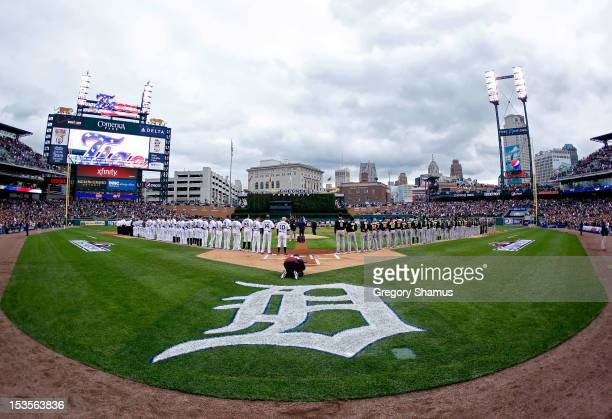 The Detroit Tigers and the Oakland Athletics line up on the baselines for the performance of the National Anthem and pregame festivities during Game...