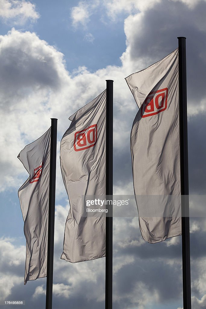 The Deutsche Bahn AG logo sits on banners flying outside Berlin Central Station, also known as Hauptbahnhof, in Berlin, Germany, on Tuesday, Aug. 13, 2013. German gross domestic product rose 0.7 percent from the first quarter and the French economy expanded 0.5 percent, the countries' national statistics offices said today. Photographer: Krisztian Bocsi/Bloomberg via Getty Images