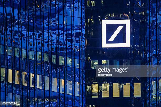 The Deutsche Bank AG logo sits illuminated on the bank's headquarter offices at dusk in Frankfurt Germany on Wednesday Jan 27 2016 German domestic...