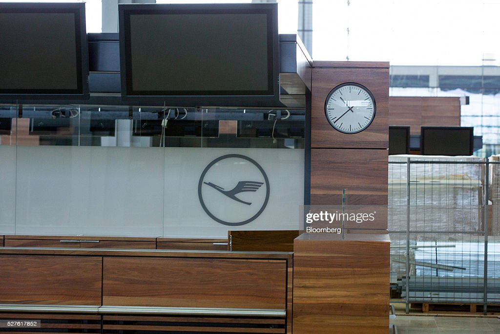 The Deutsche Lufthansa AG logo sits behind a passenger luggage check in desk inside Berlin Brandenburg International Willy Brandt Airport in Schoenefeld, Germany, on Monday, May 3, 2016. The massively overbudget airport was planned to open in 2010 and handle 27 million passengers a year, crowning Berlin as the continent's 21st century crossroads. Photographer: Krisztian Bocsi/Bloomberg via Getty Images