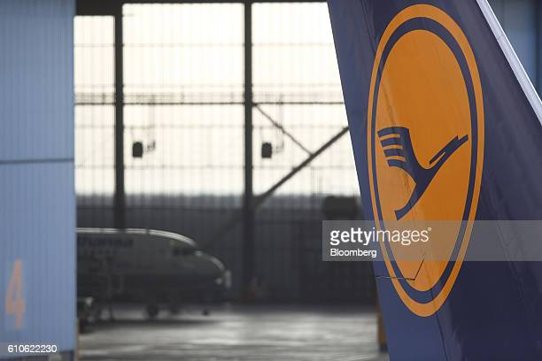 The Deutsche Lufthansa AG logo sits on the tail fin of a passenger jet as it stands outside an aircraft hangar at Frankfurt Airport operated by...