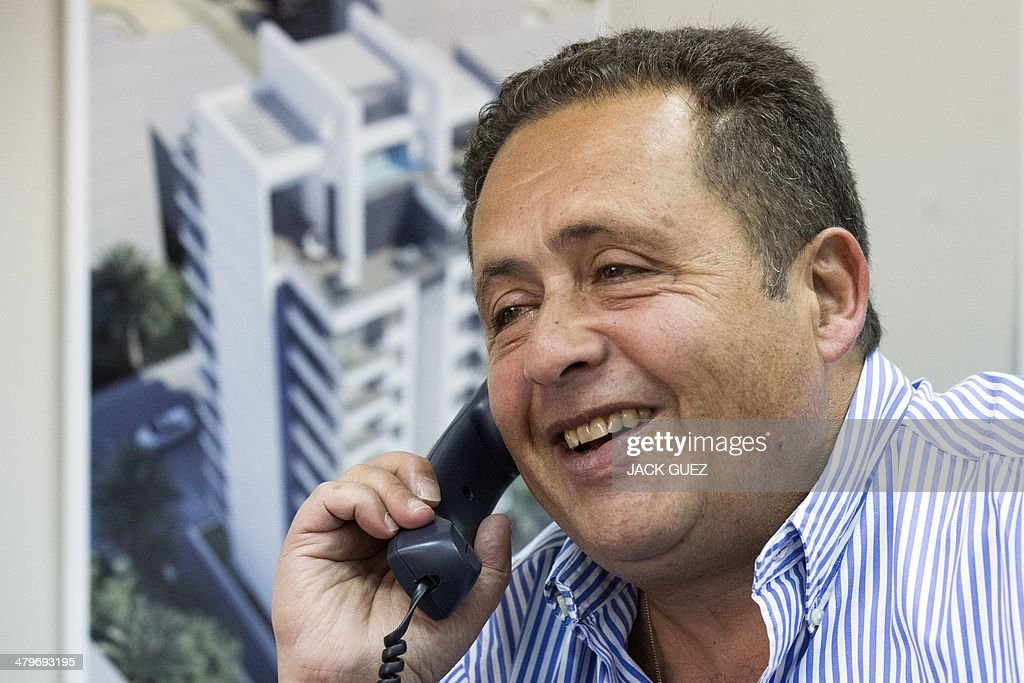 The developer and real estate agent Paul Bismith speaks on the phone at his office, on March 20, 2014 in the city of Netanya in Israel. Bismuth, a former high-school friend of Thierry Herzog, had his identity borrowed to open a second phone line to Nicolas Sarkozy, whose private telephone conversations with his lawyer Herzog have been legally traced.