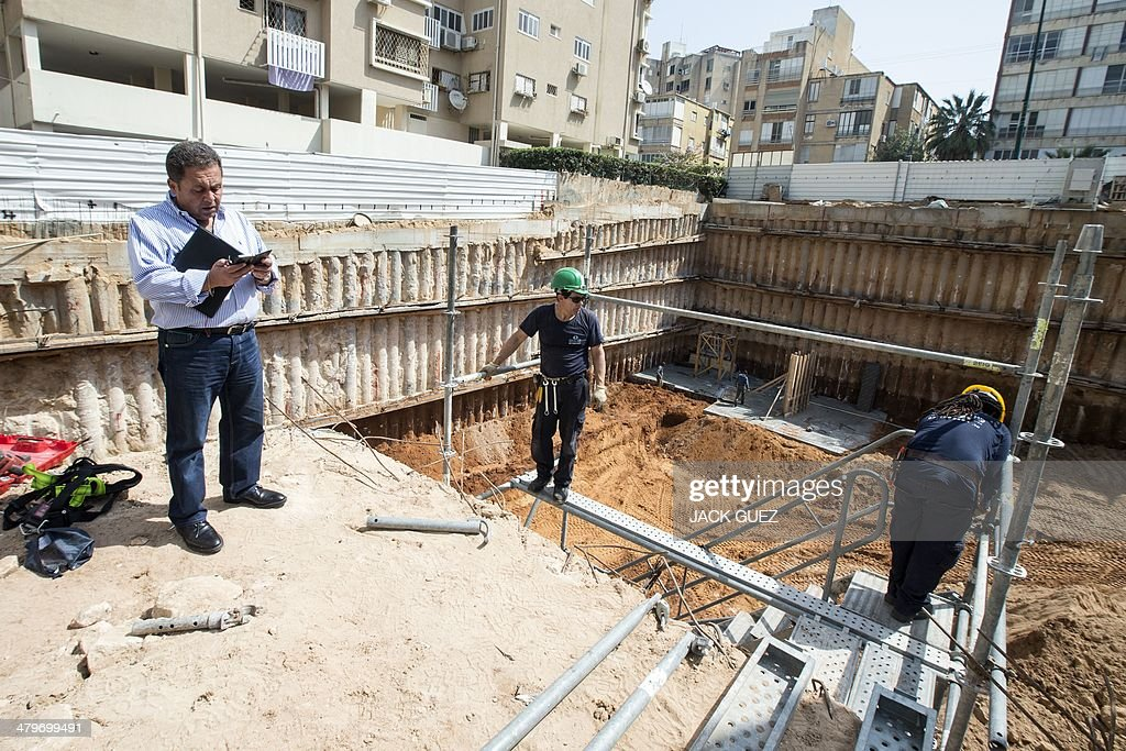 The developer and real estate agent Paul Bismuth (L) inspects his phone, on March 20, 2014 in the city of Netanya in Israel. Bismuth, a former high-school friend of Thierry Herzog, had his identity borrowed to open a second phone line to Nicolas Sarkozy, whose private telephone conversations with his lawyer Herzog have been legally traced.