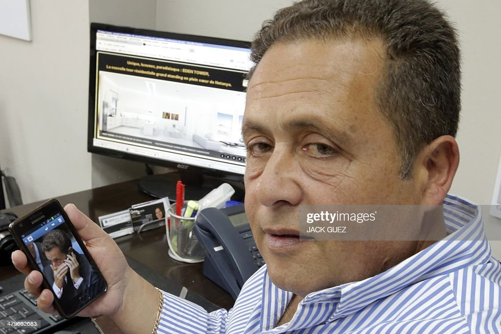 The developer and real estate agent Paul Bismuth looks at a picture of former French president Nicolas Sarkozy on a mobile phone, on March 20, 2014 in the city of Netanya in Israel. Bismuth, a former high-school friend of Thierry Herzog, had his identity borrowed to open a second phone line to Nicolas Sarkozy, whose private telephone conversations with his lawyer Herzog have been legally traced.
