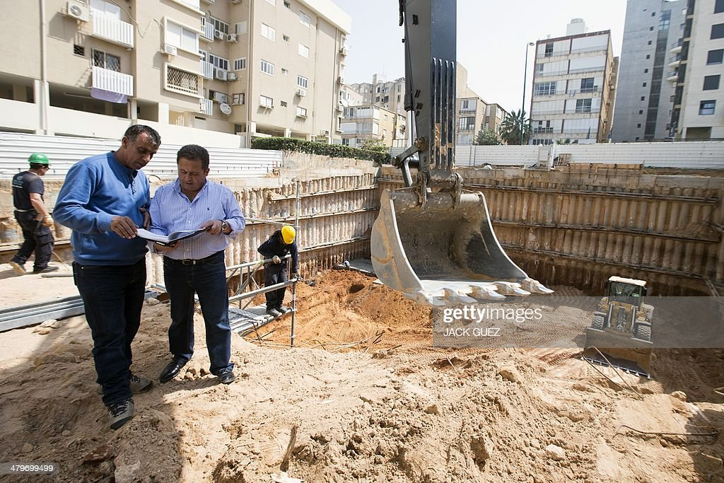 The developer and real estate agent Paul Bismuth (3rd-L) talks with the construction site foreman, on March 20, 2014 in the city of Netanya in Israel. Bismuth, a former high-school friend of Thierry Herzog, had his identity borrowed to open a second phone line to Nicolas Sarkozy, whose private telephone conversations with his lawyer Herzog have been legally traced.