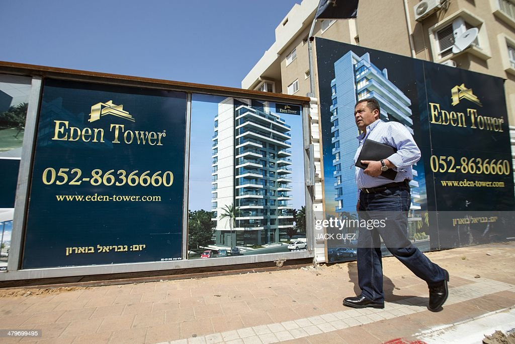 The developer and real estate agent Paul Bismuth walks past a billboard, on March 20, 2014 in the city of Netanya in Israel. Bismuth, a former high-school friend of Thierry Herzog, had his identity borrowed to open a second phone line to Nicolas Sarkozy, whose private telephone conversations with his lawyer Herzog have been legally traced.