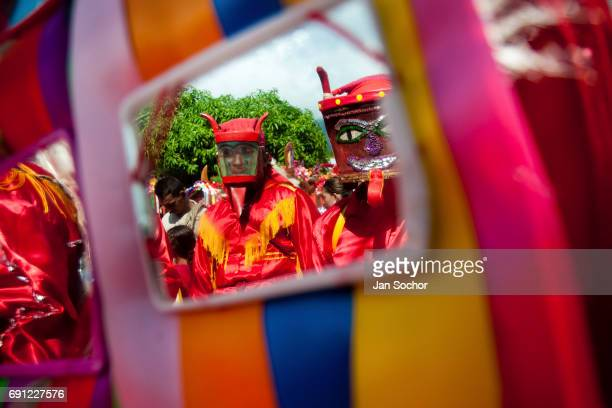 The Devils shown in the mirror during the religious procession as part of Dancing Devils Festival on June 03 2010 in Atanquez Sierra Nevada Colombia...
