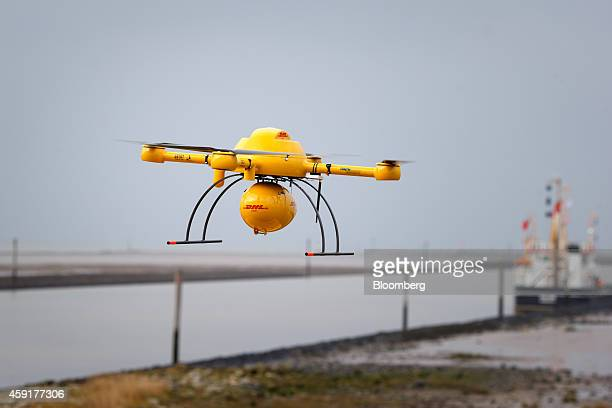 The DHL logo sits on a parcel delivery drone manufactured by Microdrones GmbH as it flies during testing by Deutsche Post AG's parcel delivery unit...